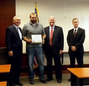 Freedom Alliance President Tom Kilgannon presents a certificate and title to a new home for a wounded soldier.