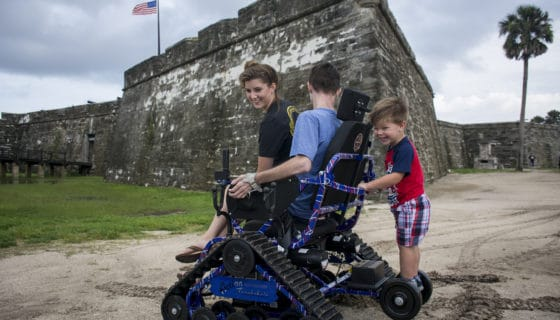 Man rides trackchair with wife and son.